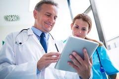 Médecin et infirmière discutant au-dessus du comprimé numérique photos libres de droits