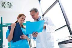 Médecin et infirmière vérifiant le rapport médical images libres de droits