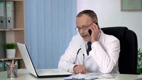 Médecin expérimenté parlant au téléphone, patient de consultation au sujet de traitement images libres de droits