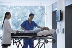Médecin féminin et infirmière roulant une civière avec un patient dans les halls de l'hôpital Photo stock