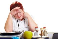 Médecin féminin fatigué avec le grillage Images libres de droits