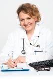 Médecin féminin heureux au bureau de travail photos libres de droits