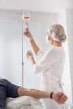 Médecin féminin préparant le compte-gouttes pour l'homme photos stock