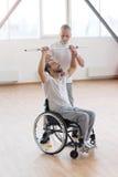 Médecin généraliste âgé sérieux enseignant l'handicapé dans le gymnase Photographie stock libre de droits