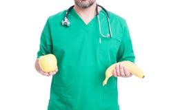 Médecin inconnu tenant la pomme et une banane Photographie stock