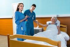 Médecin masculin attirant et infirmière féminine mesurant l'impulsion et Images libres de droits