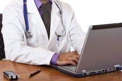 Médecin observant ses notes sur l'ordinateur portatif Images libres de droits