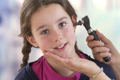 Médecin OTO-RHINO vérifiant l'oreille patiente du ` s utilisant l'otoscope images stock