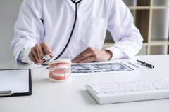 Médecin ou dentiste masculin vérifiant la maladie de dents dans le modèle dentaire et l'équipement utilisés dans le traitement de image stock
