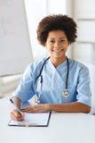 Médecin ou infirmière féminin heureux écrivant au presse-papiers Image stock