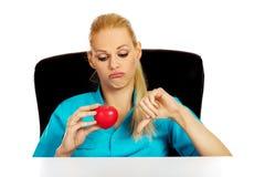 Médecin ou infirmière féminin inquiété s'asseyant derrière le bureau tenant le modèle de coeur et montrant le pouce vers le bas images stock