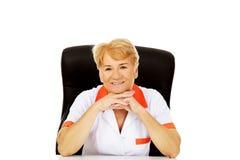 Médecin ou infirmière féminin plus âgé de sourire s'asseyant derrière le bureau se penchant sur des mains Photographie stock
