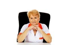 Médecin ou infirmière féminin plus âgé de sourire s'asseyant derrière le bureau se penchant sur des mains Photo libre de droits