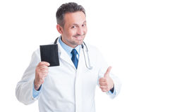 Médecin ou médecin de sourire tenant le portefeuille et montrant comme Photographie stock libre de droits