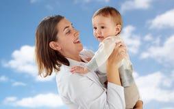 Médecin ou pédiatre heureux avec le bébé au-dessus du ciel images libres de droits