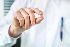 Médecin ou pharmacien tenant une pilule entre les doigts photo stock