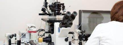 Médecin ou scientifique travaillant avec l'ordinateur et le microscope dans le laboratoire biotechnologique Équipement dans le la images stock