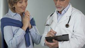 Médecin praticien donnant de bonnes actualités au patient féminin, progrès de traitement banque de vidéos