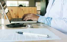 Médecin professionnel dans le manteau uniforme blanc de robe fonctionnant l images libres de droits