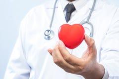 Médecin professionnel tenant une boule rouge de coeur dans le hosp Photos libres de droits