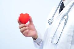 Médecin professionnel tenant une boule rouge de coeur dans le hosp Images libres de droits