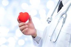 Médecin professionnel tenant une boule rouge de coeur sur la tache floue  Photographie stock libre de droits