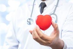 Médecin professionnel tenant une boule rouge de coeur sur la tache floue  Photos libres de droits