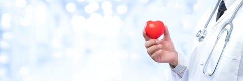 Médecin professionnel tenant une boule rouge de coeur sur la tache floue  Photo libre de droits
