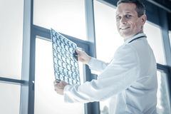 Médecin qualifié sûr souriant et tenant le balayage de rayon X Images stock