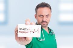 Médecin sérieux tenant la carte d'affaires ou de visite photo stock