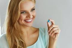 médecine Belle femme de sourire prenant la pilule de médicament Images stock