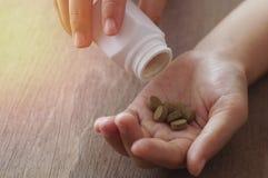 médecine d'herbe dans la pilule et puring de la bouteille blanche photos libres de droits