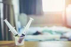 Médecine de deux liquides avec seringues dans une tasse de mesure cru Image stock