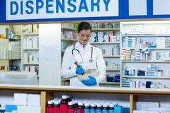 Médecine de meulage de pharmacien dans le mortel et le pilon au compteur photographie stock