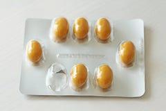 Médecine jaune ou orange de pilule de capsule sur le fond blanc Médecine de pilules d'antibiotiques de pharmaceutiques photographie stock