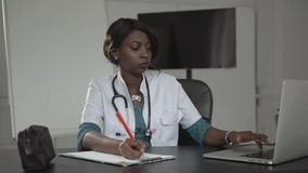Médecine, les gens et concept de soins de santé - médecin ou infirmière féminin heureux d'afro-américain rédigeant le rapport méd clips vidéos