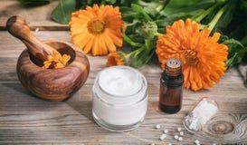 Médecine normale Huile essentielle, onguent un mortier et pilules blanches sur une table en bois, fond de floraison frais de cale photographie stock libre de droits