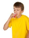 Médecine potable de garçon sur le blanc Images stock