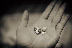 Médecine pour réduire la fièvre froide à disposition Beaucoup de pilules multi de forme dans des mains d'un aîné Soins douloureux image stock