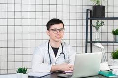 Médecine, profession, technologie et concept de personnes - docteur masculin de sourire avec l'ordinateur portable dans le bureau photographie stock libre de droits