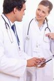Médecins auxiliaires parlant de ce qui est sur la tablette photos libres de droits
