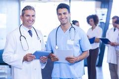 Médecins avec le comprimé numérique et le rapport médical regardant l'appareil-photo et le sourire Images libres de droits