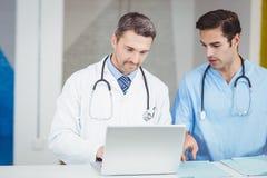 Médecins concentrés travaillant sur l'ordinateur portable Photos libres de droits