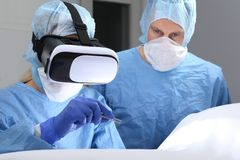 Médecins dans la chirurgie de salle d'opération avec la réalité virtuelle photos libres de droits