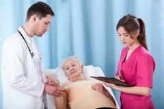 Médecins diagnostiquant la femme agée Image libre de droits