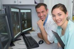 Médecins du portrait deux souriant dans la chambre de surveillance dans l'hôpital Images libres de droits