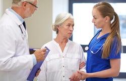 Médecins et femme patiente supérieure à l'hôpital Images stock