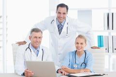 Médecins et infirmière de sourire regardant l'appareil-photo devant l'ordinateur portable Photo stock