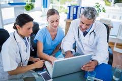 Médecins et infirmière regardant l'ordinateur portable images libres de droits