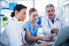 Médecins et infirmière regardant l'ordinateur portable Photographie stock libre de droits